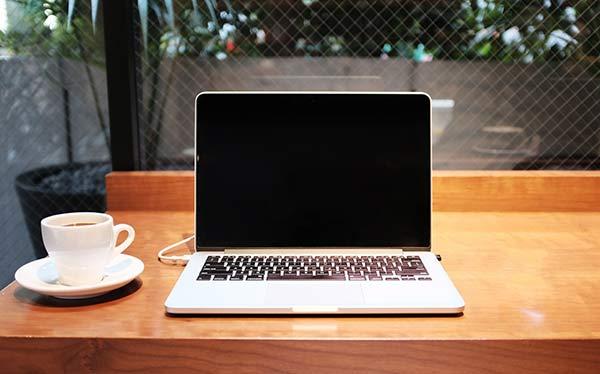 カフェでノートパソコンとコーヒーカップが置いてある写真
